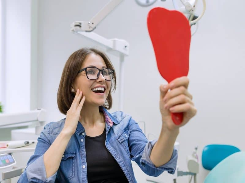 Canva Woman Patient Looking in the Mirror at the Teeth Sitting in the Dental Chair. Healthcare Medical and Dentistry Concept 1