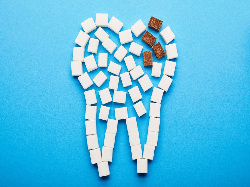Canva top view of white and brown sugar cubes arranged in tooth sign on blue background dental caries concept 1