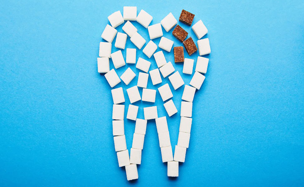 Canva top view of white and brown sugar cubes arranged in tooth sign on blue background dental caries concept