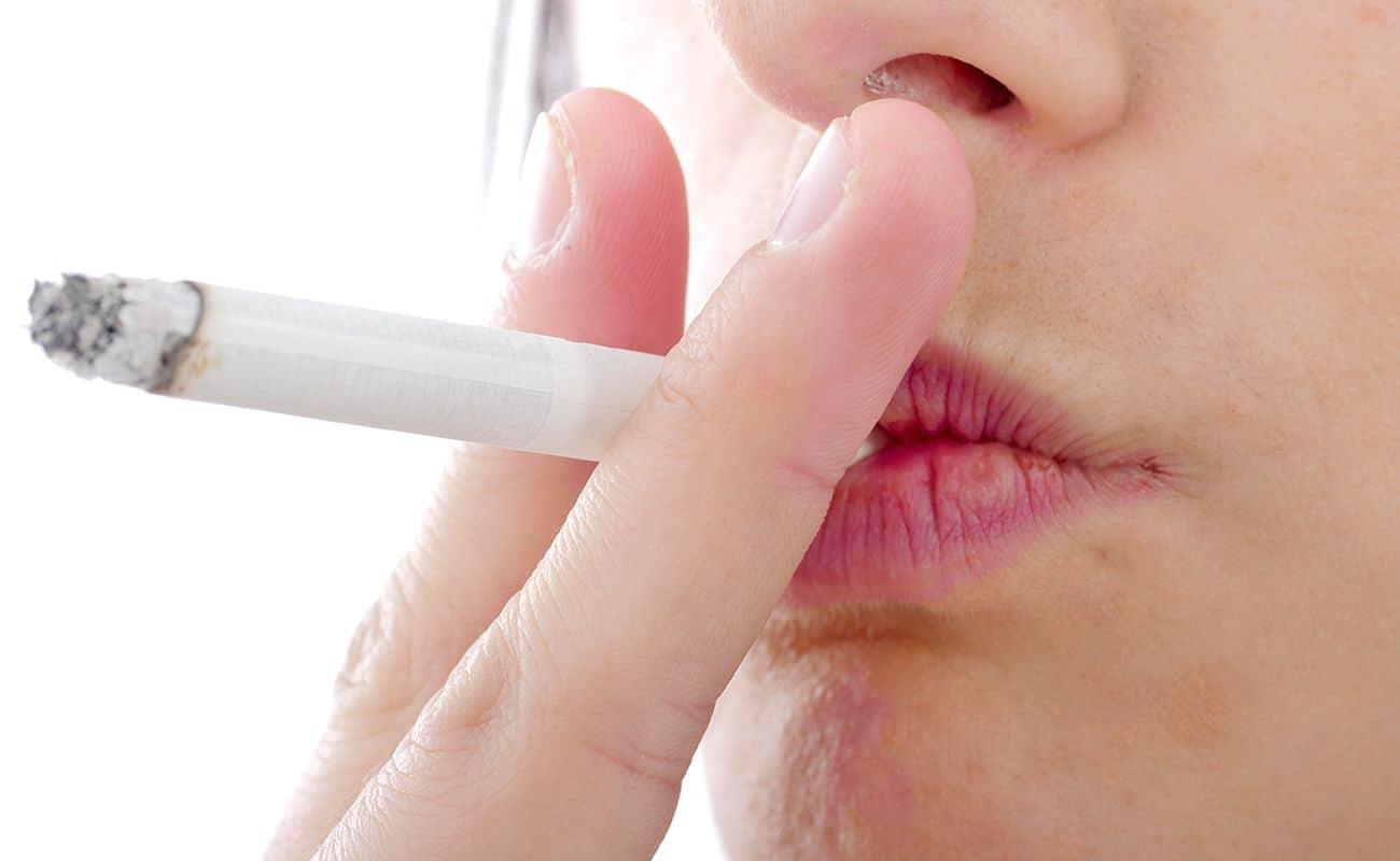 cigarro en boca de persona periodoncia e implantes monterrey