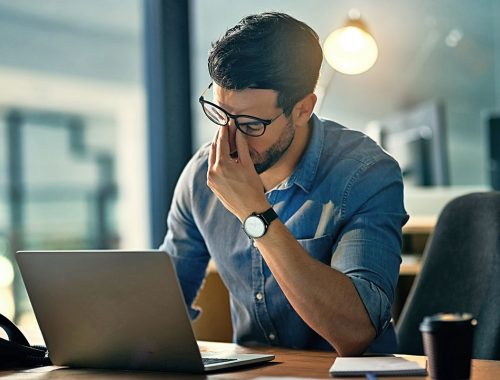 hombre con laptop cansado periodoncia e implantes monterrey