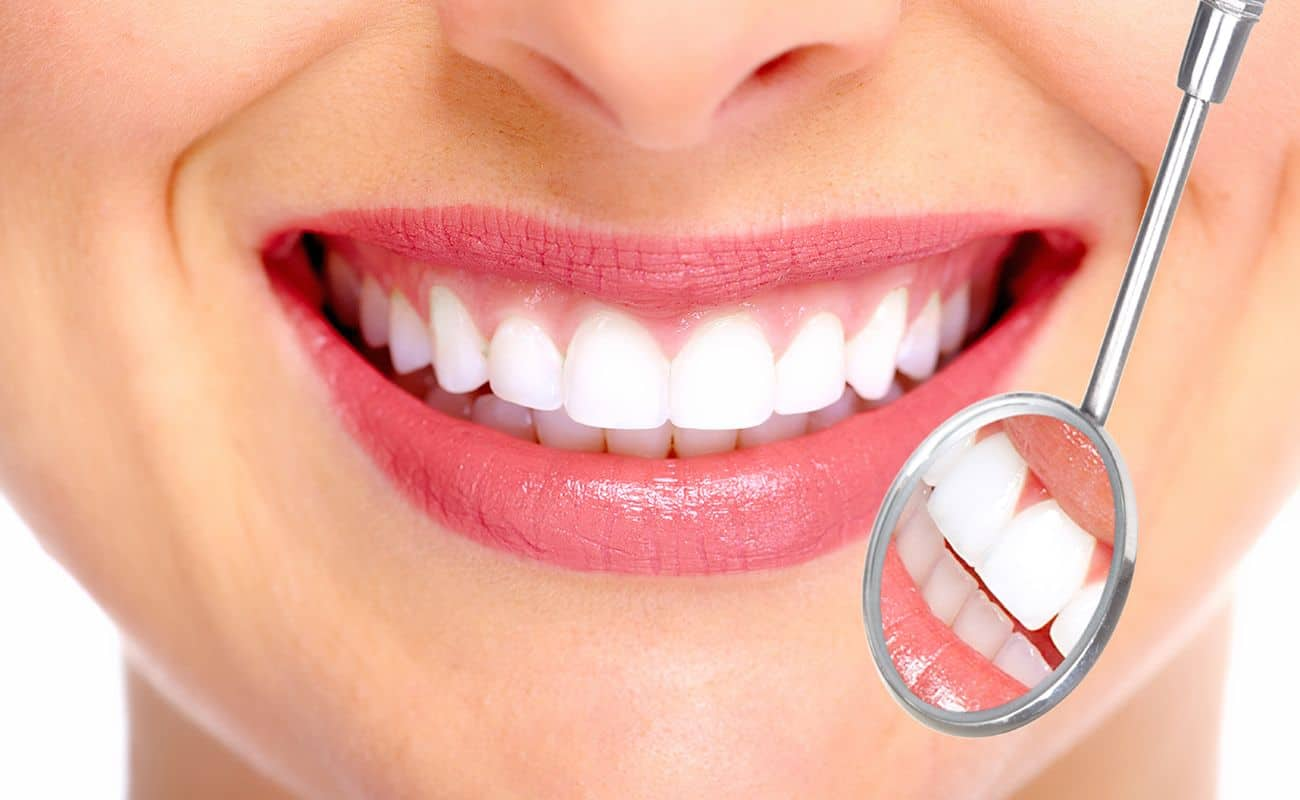 sonrisa con espejo de dentista periodoncia e implantes monterrey
